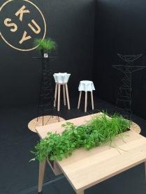 Stolek s bylinkami, v pozadí stolička-stolek-květináč-mísa...a české stožáry vysokého napětí jako stojany na kytky... Design kusy
